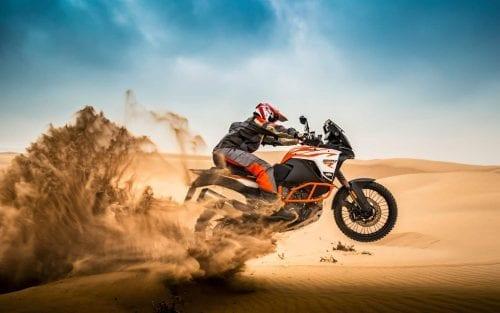 KTM rider on KTM motorcycle doing a wheelie through desert