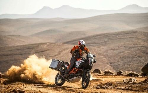 KTM rider on KTM motorcycle with dust cloud behind him