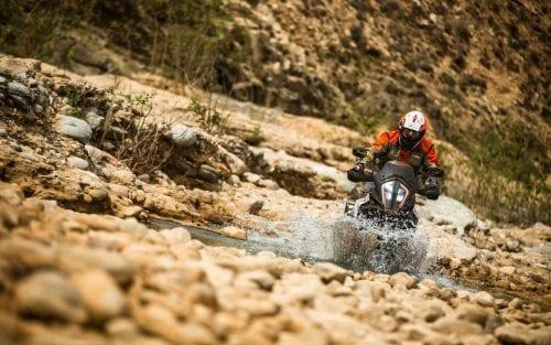KTM rider, riding through stream