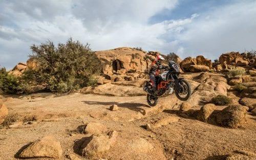 KTM rider in air going off rocks