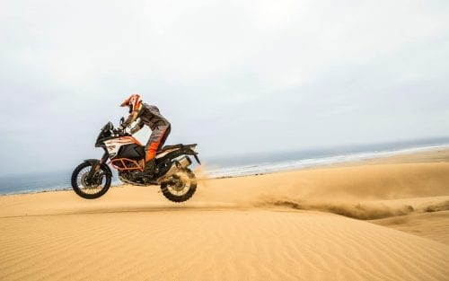 KTM rider in mid air after coming up over top of dune