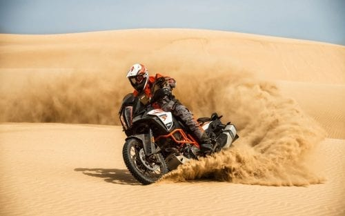 KTM rider spinning up the sand in the desert