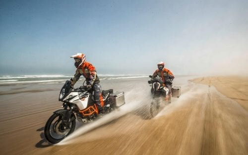 Two KTM riders riding through the waves on the beach