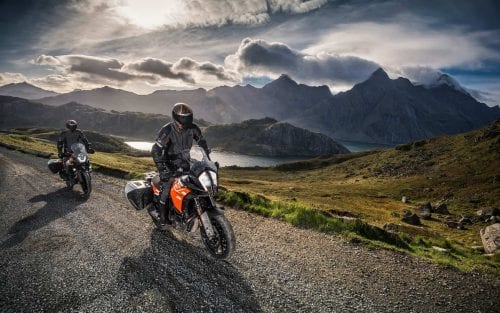 Two KTM riders riding on gravel road next to river